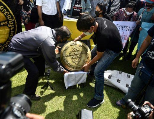 Les manifestants apposent la plaque symbolique devant le grand palais