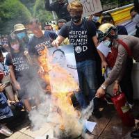 Portrait du general prayut chan o cha brule tandis qu un soldat tente d etendre l incendie qui menace la monarchie