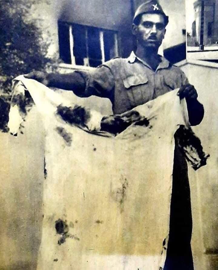 Un soldat exhibe les vêtements du roi faysal ii