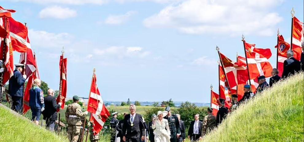 La reine Margrethe II sous une haie de drapeaux nationaux